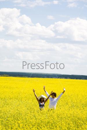 Радостная пара стоит летом в поле цветов и поднимает руки
