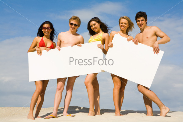 Фотография на тему Компания веселых друзей держит белые плакаты на песчаном пляже