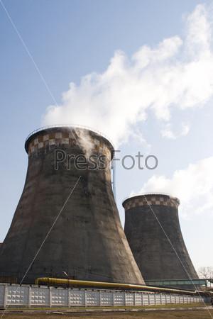 Фотография на тему Современный промышленный завод с выхлопными трубами за забором