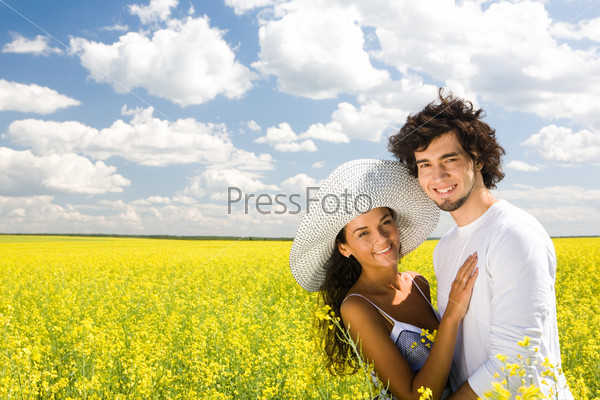 Молодая пара обнимается в поле желтых цветов