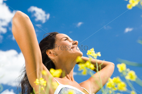 Красивая девушка улыбается, наслаждаясь солнцем на природе