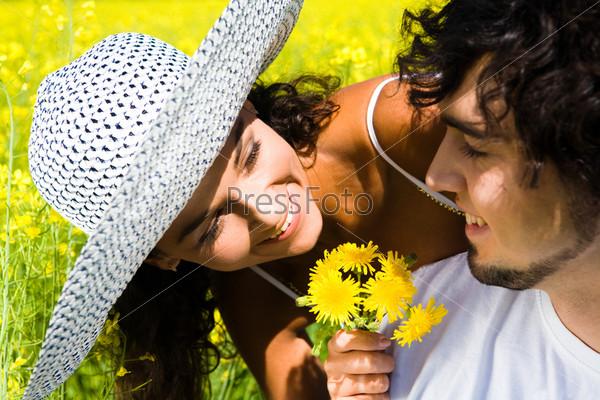 Улыбающаяся девушка показывает букет желтых одуванчиков симпатичному парню, который смотрит на нее