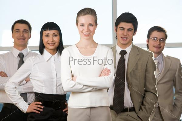Успешная команда молодых менеджеров стоит в офисе и улыбается в камеру