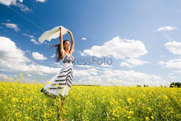 Счастливая девушка стоит в желтом поле и держит над собой белую ткань