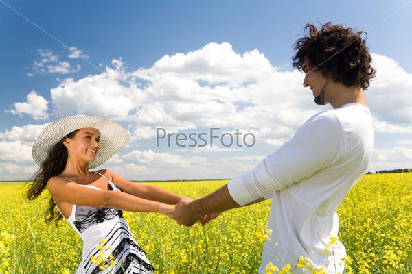 Привлекательная пара держится за руки и кружится в поле