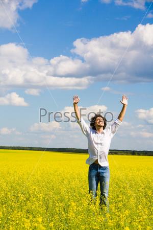 Беззаботный молодой человек в поле поднимает руки и наслаждается летним днем
