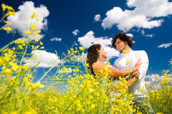 Влюбленные в золотистом поле под летним облачным небом