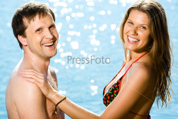 Счастливая пара улыбается на фоне моря