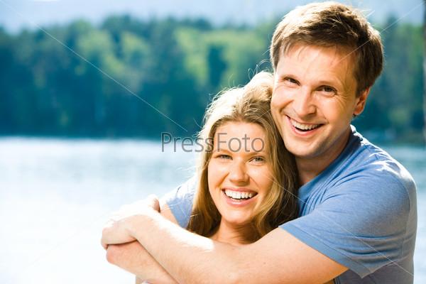 Улыбающийся мужчина обнимает красивую женщину