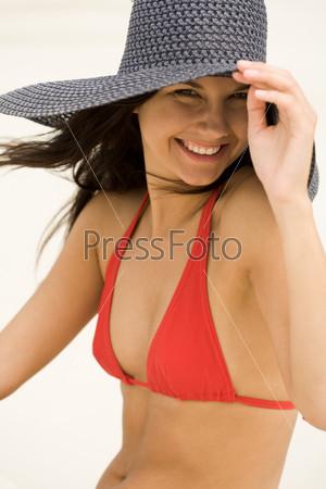 Красивая девушка в купальнике смотрит в камеру и улыбается