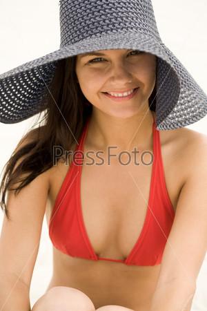 Элегантная девушка в купальнике и большой шляпе смотрит в камеру с улыбкой