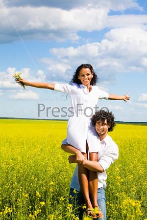 Счастливый парень стоит в поле желтых цветов и держит девушку на плечах