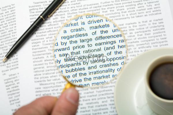 Рука, держащая увеличительное стекло над газетой со стоящей рядом чашкой кофе