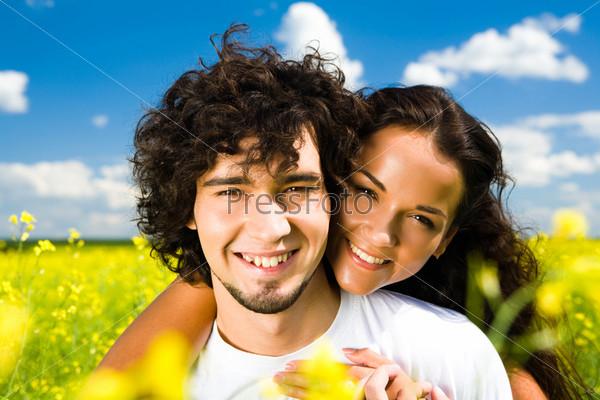 Счастливая девушка обнимает парня и оба улыбаются летним днем