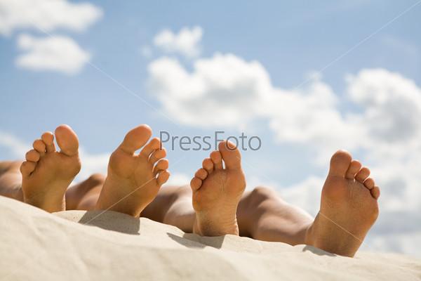 Крупный план босых ног лежащих на песке