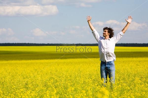 Довольный парень в рубашке и джинсах понимает вверх руки и смотрит в небо