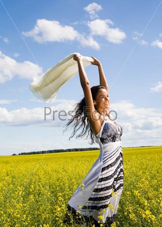 Красивая девушка с улыбкой на лице стоит в поле и смотрит вдаль
