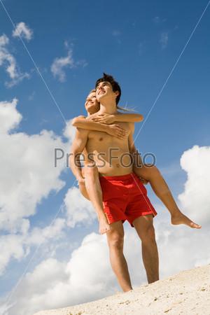 Молодой человек держит на спине свою подругу стоя на песке на фоне голубого неба