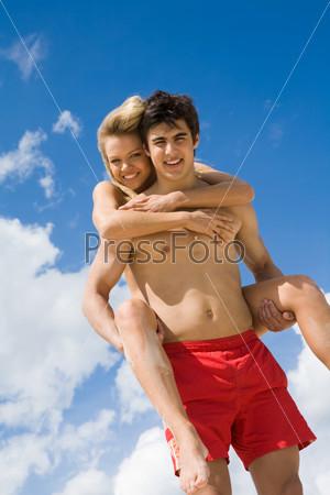 Молодой человек катает свою подругу на спине на природе