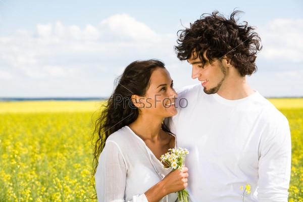 Парень обнимает девушку с букетом ромашек на фоне летнего пейзажа