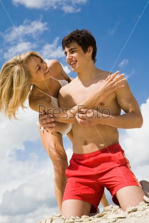 Девушка нагнулась к молодому человеку стоящему на коленях на песке