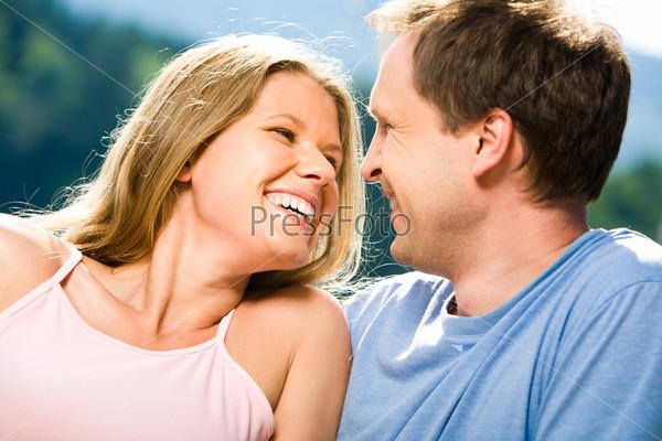 Радостная женщина смеется и смотрит на улыбающегося мужчину