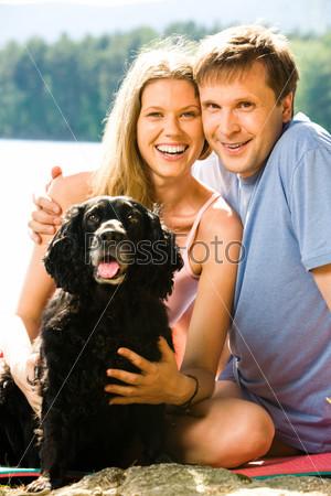 Счастливый муж обнимает красивую жену, рядом с ними сидит собака