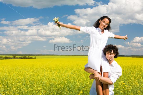 Молодой человек стоит на фоне летнего пейзажа и держит на руках счастливую девушку