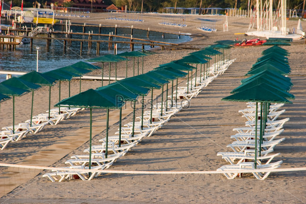 Фото длинных рядов шезлонгов под зонтами на побережье