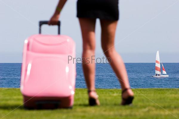 Женские ноги стоящие рядом с розовым чемоданом на фоне яхты на морской глади