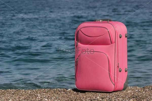 Розовый чемодан на берегу на фоне морской воды