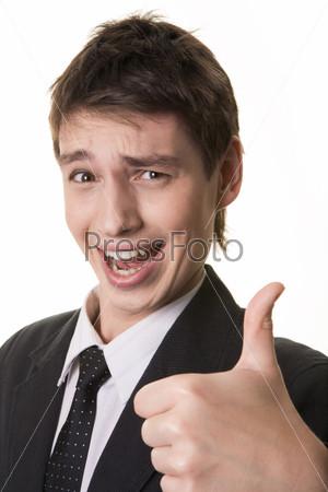 Уверенный молодой человек показывает знак Окей и смотрит в камеру