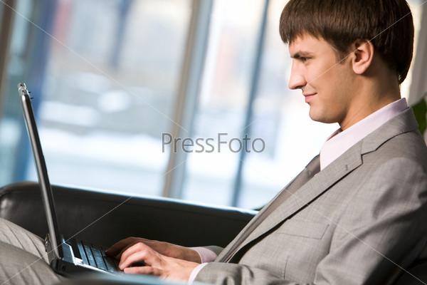 Успешный менеджер печатает и смотрит на экран ноутбука