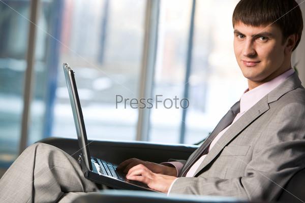 Привлекательный мужчина печатает на клавиатуре ноутбука