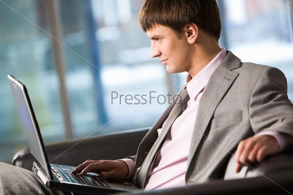 Бизнесмен с ноутбуком в офисе
