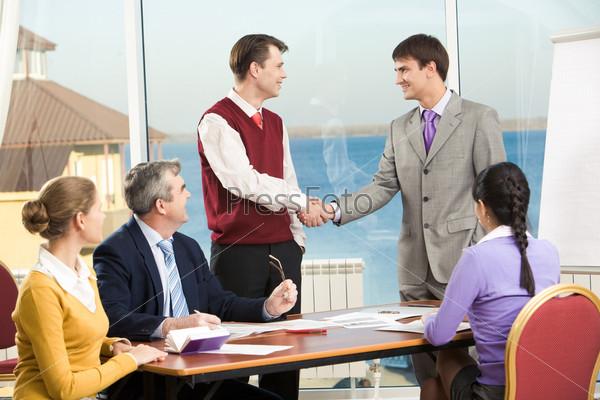 Партнеры смотрят на успешных сотрудников, которые пожимают друг другу руки