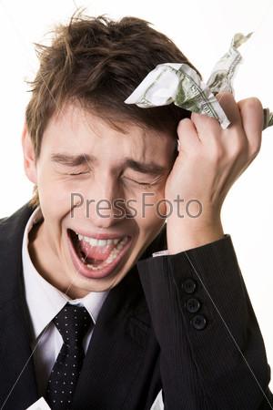 Бизнесмен со смятым долларом в руке схватился за голову