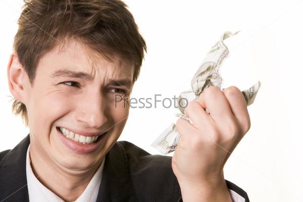 Молодой человек злобно смотрит на смятую в руке банкноту доллара