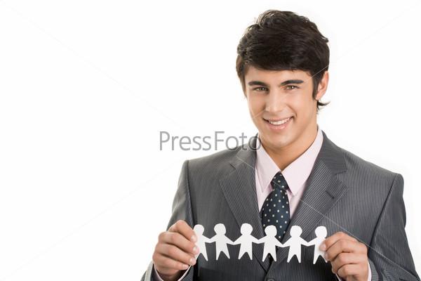 Счастливый бизнесмен держит в руках цепь вырезанных из бумаги фигурок