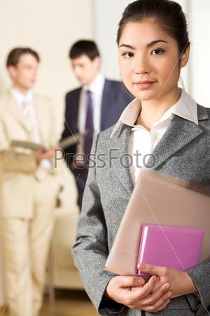 Симпатичная девушка держит в руках папку и блокнот