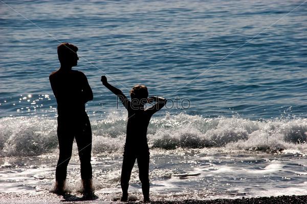 Папа с сыном стоят в воде у береговой линии моря