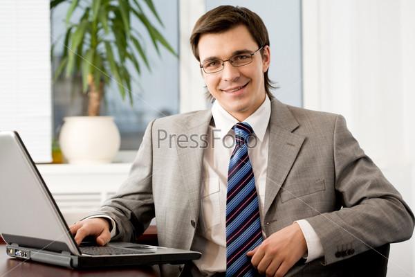 Уверенный бизнесмен в очках смотрит в камеру и улыбается