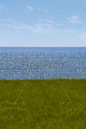 Зеленая поляна на фоне моря в солнечный летний день