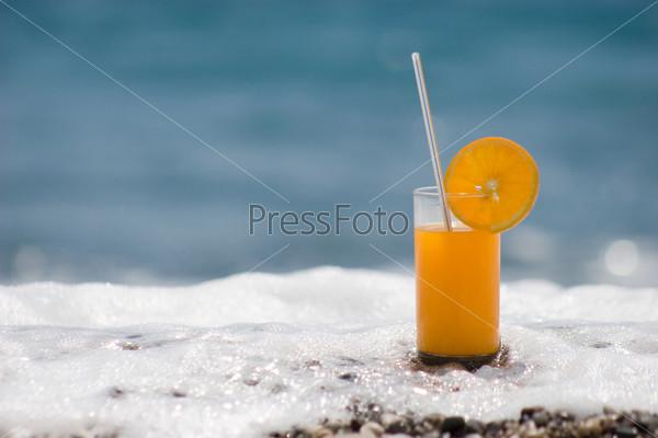 Стакан апельсинового сока омытый морской пеной на берегу