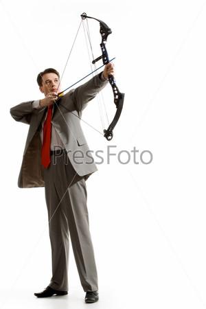 Мужественный бизнесмен держит арбалет и целится вверх