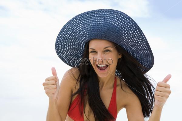 Эмоциональная девушка в купальнике и шляпе смеется глядя в камеру