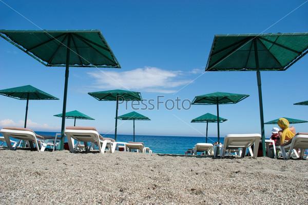 Ряды шезлонгов на набережной на фоне моря