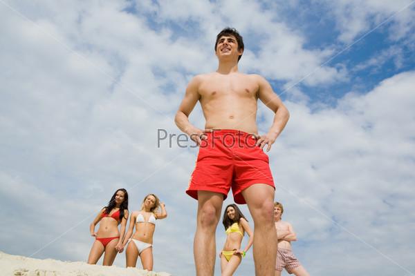 Парень в красных шортах стоит на песке на фоне компании друзей