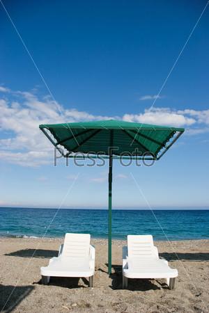 Фотография на тему Два шезлонга под зонтиком на фоне моря