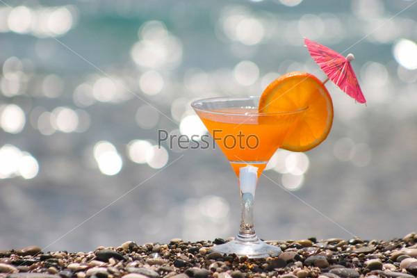 Бокал апельсинового сока стоящего на гальке на фоне моря